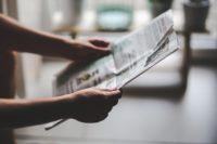 Hands holding a newspaper