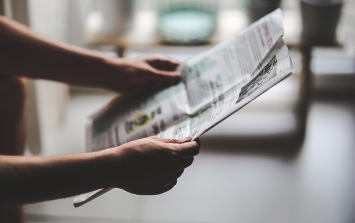 Hands holding a newspaper